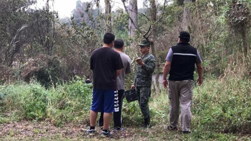 台湾军方一架无人机8日在屏东县一所小学旁的树林坠毁引发火情。军警人员封锁现场调查。图片来源:《联合报》