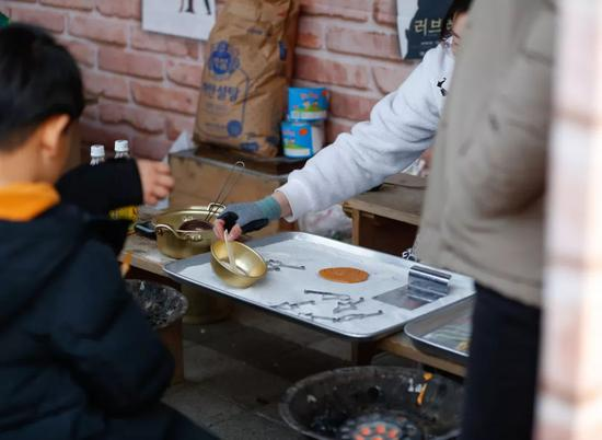 2月5日,在韩国京畿道龙仁市的韩国民俗村,小朋友观看制作传统的糖饼。新华社记者王婧嫱摄