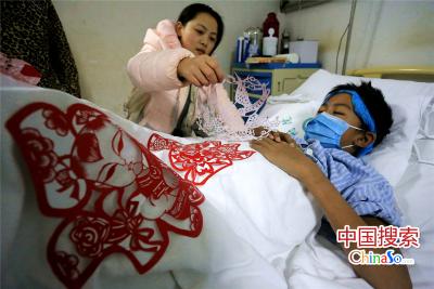 2016年1月5日,河南郑州,19岁的周口幼儿师范学校14级学生李婉君在弟弟的病床前剪剪纸。(中国搜索 杨正华 摄)