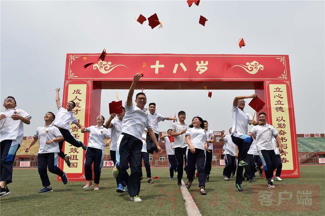 """6月18日,在沁阳市衡中河南分校永威高中高三成人礼上,学生将""""成人帽""""高高抛起,庆祝自己长大成人。当日,该校为高三中学生举办了一场特殊的集体""""成人礼"""",并邀请他们的父母一起参加,见证自己孩子的长大成人。在仪式中,这些高三中学生由自己的父母亲手为自己戴上象征长大成人的""""成人帽"""",并在父母、老师的见证下进行成人宣誓,他们还在父母的陪伴下跨过""""成人门"""",携手奔向属于自己的未来。(杨志强 鄂明 摄影)"""