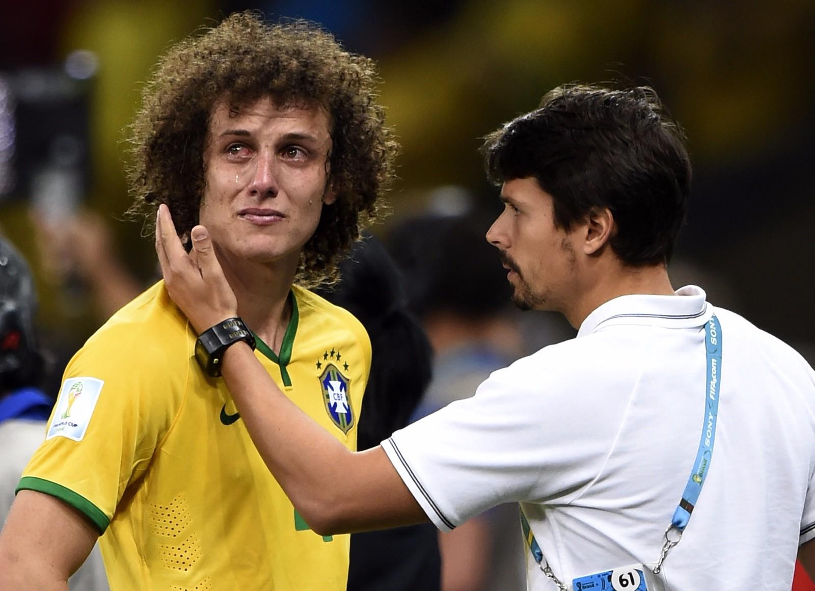 """2014巴西世界杯半决赛,巴西队以1比7不敌德国队,无缘决赛。巨大的分差让球迷们无法接受,""""米内罗惨案""""让世界杯成为巴西的""""世界悲""""。比赛结束后,巴西队队长大卫·路易斯(左)泪流满面(2014年7月8日摄)。"""