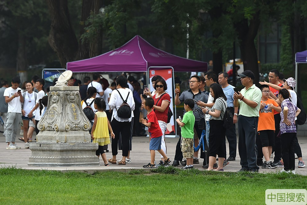2019年7月17日,北京,暑期已经拉开帷幕,清华大学又一次迎来参观高峰期,来自全国各地的学生及老师家长进校参观游览,一睹名校风采。图为清华日晷吸引众多游客参观。中国搜索宋家儒摄