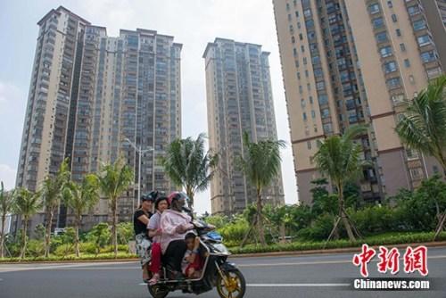 资料图:市民在海口市区某地产项目前路过。 <a target='_blank' href='http://www.chinanews.com/'>中新社记者 骆云飞 摄